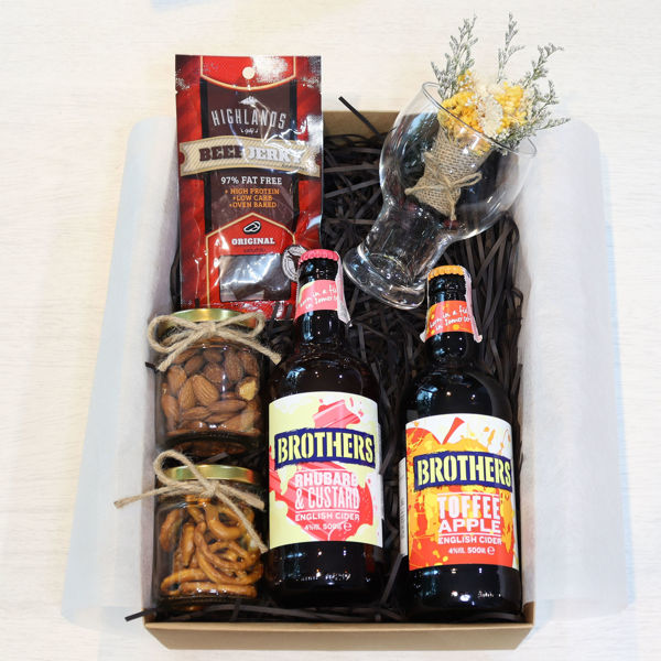A couple of different flavored ciders  with bar snacks all nicely placed in a gift box.