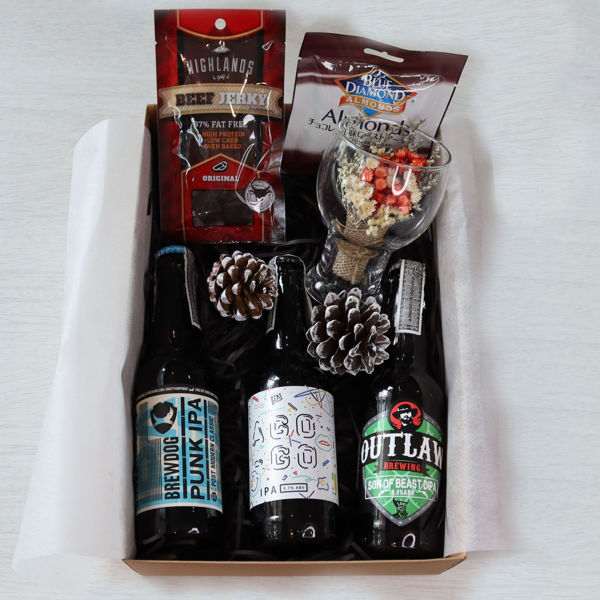 A gift box for IPA lovers containing three different IPA beers, some salty bar snacks and a mini bouquet of flowers