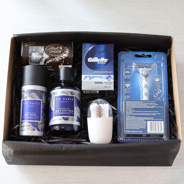 A gift box for men with a Gillette razor and aftershave set, Tom Baker body wash and spray, cotton buds with a storage box and some Lindt Lindor dark chocolates.