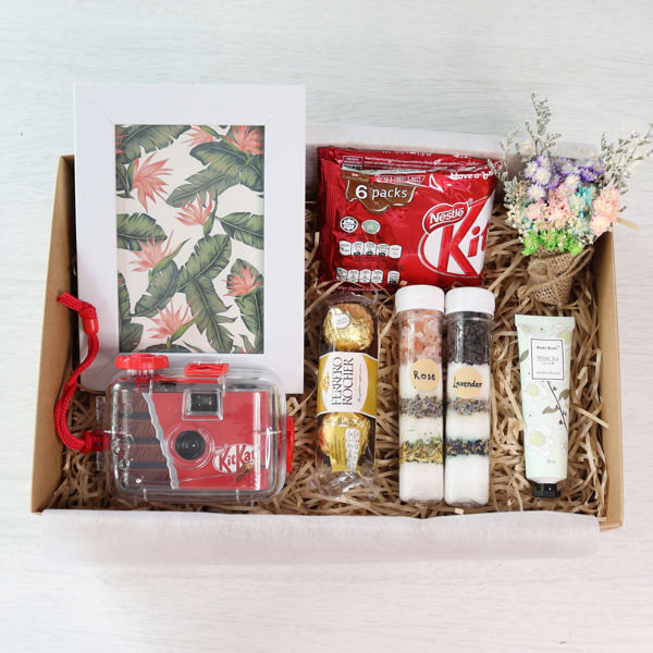 A vacation gift box set with a red underwater film camera, picture frame, bath salts, hand cream, chocolates and flowers