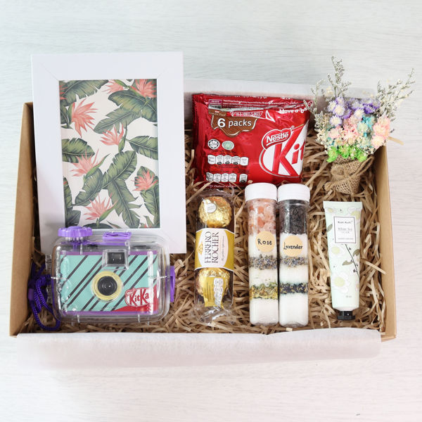 A vacation gift box set with a blue underwater film camera, picture frame, bath salts, hand cream, chocolates and flowers