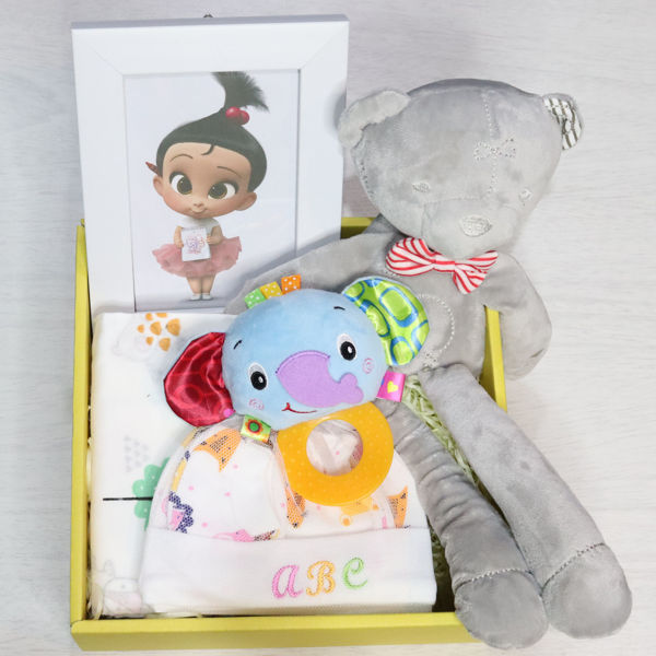 A gift set box for babies with a teddy bear, clothing and a picture frame