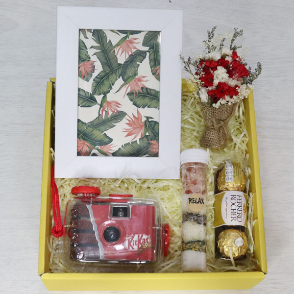 A gift box for people going on vacation with a red waterproof camera, picture frame, bath salts with rose flowers, flowers and chocolate