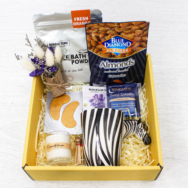 A gift box for people who have trouble sleeping. It contains calming teas with a mug, bubble bath, eye pads, an aromatherapy candle, matches and some chocolates with a mini-bouquet of flowers