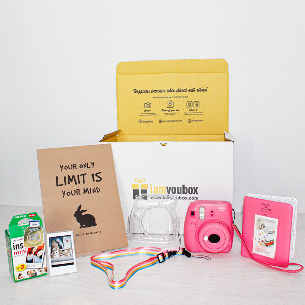 A gift set with a Fujifilm polaroid camera, protective case, photo album, picture frame and two packs of polaroid photo film
